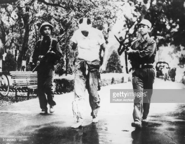 American POW L Hughes a lieutenant colonel in the US Air Force is paraded barefoot and with a bandaged face through the street by two Vietnamese...