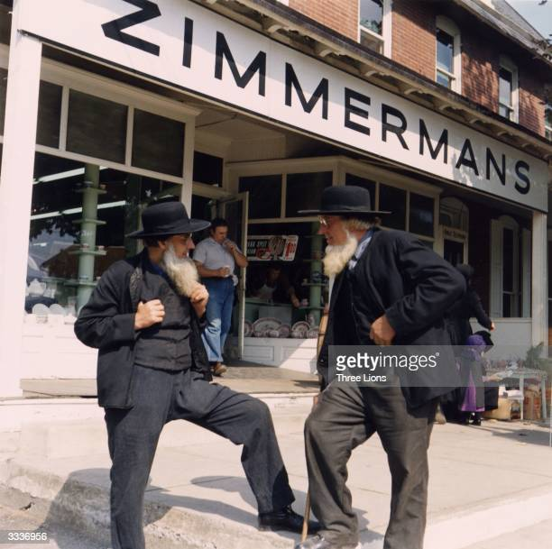 Amish men talk during a trip into town They wear the garb of the Pennsylvania Dutch a symbol of their nonconformity to modern society