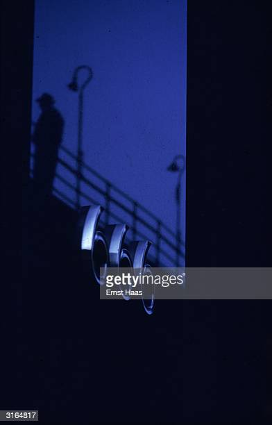 An evening in New York City with a silver coloured sign '666' shining in the dusk below the silhouette of railings and a lamppost