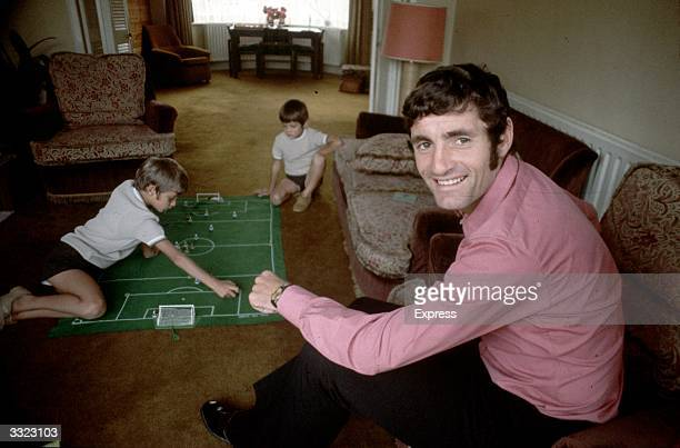 Arsenal footballer Frank McLintock at home watching his children playing the football game Subbuteo.