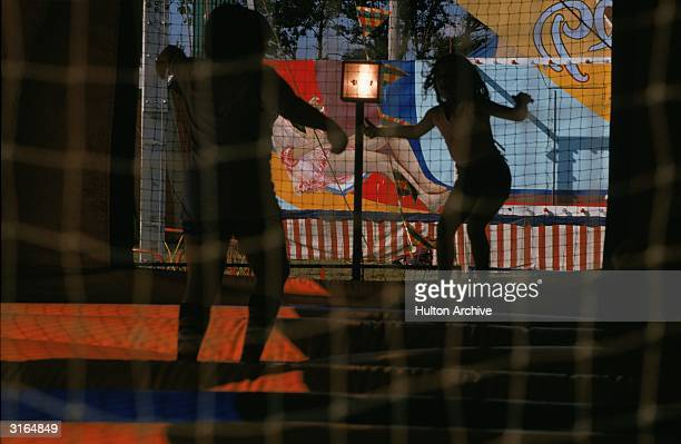Children dancing round a sun lamp against a backdrop of reflections trees and a poster behind netting