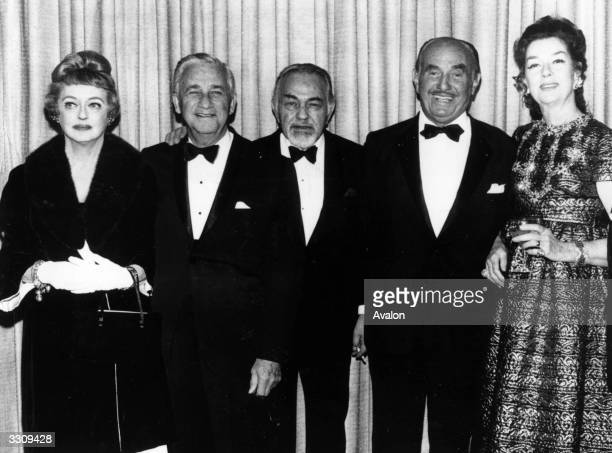 From left to right Bette Davis Mervyn Leroy Edward G Robinson Jack Warner and Rosalind Russell They are all gathered together to pay tribute to Jack...