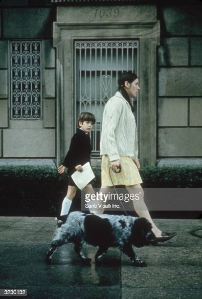 Future American lawyer and magazine publisher John F Kennedy Jr walks with his nanny and pet spaniel on a city sidewalk as a young boy New York City