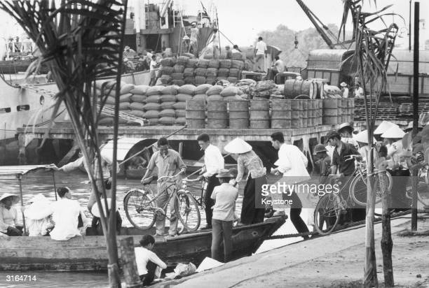 Passengers boarding a ferry boat to cross the Saigon River while rice and kerosene are unloaded in the background
