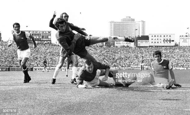 Peter Osgood of Chelsea leaps over Arsenal goalkeeper Bob Wilson during their match at Stamford Bridge