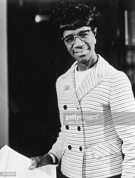 Portrait of US congresswoman Shirley Chisholm wearing a striped suit and cat'seye glasses holding a copy of The Congressional Record and smiling
