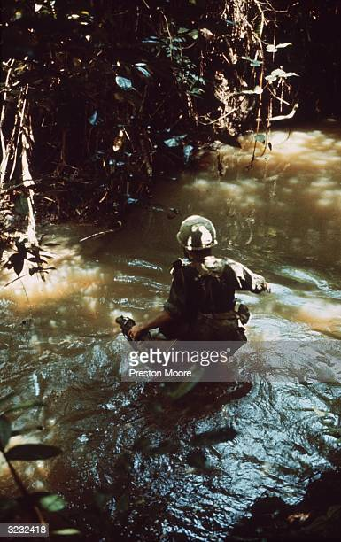 Rear view of a soldier wading waisthigh through a river during combat in the Vietnam War