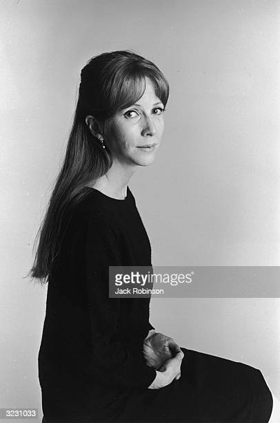 Studio portrait of American actor Julie Harris wearing a dark sweater and sitting with her hands in her lap