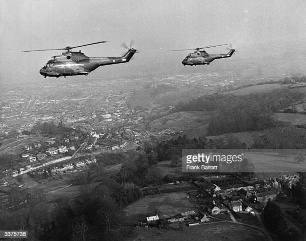 Two Westland 'Puma' helicopters in army camouflage flying over Yeovil Somerset