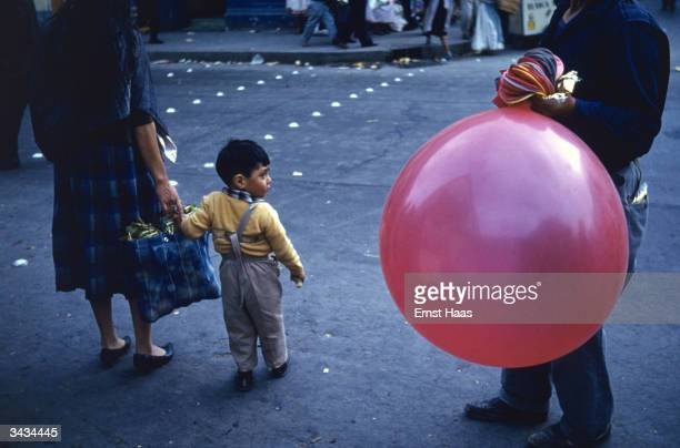 Waiting to cross the street in New York a little boy's attention is caught by a vendor with a large balloon