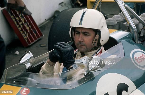 Australian racing driver Jack Brabham behind the wheel at Brands Hatch