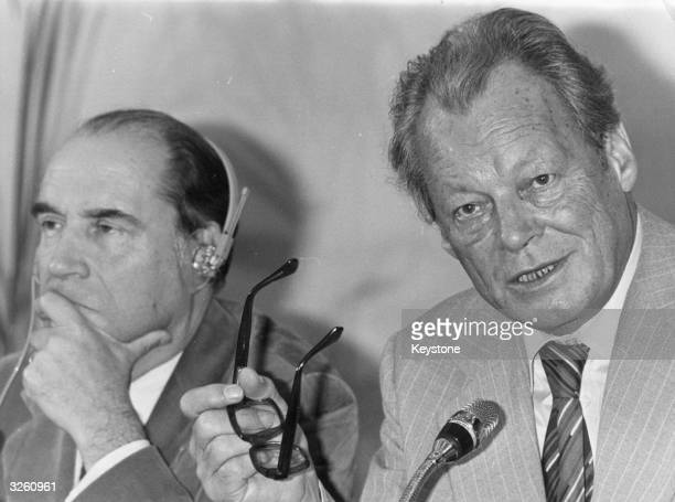 German Chancellor Willy Brandt and French politician Francois Mitterrand at an International Socialist meeting in Paris