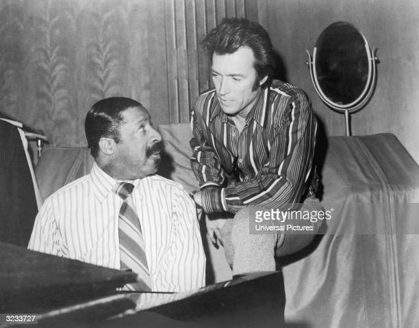 American actor Clint Eastwood looks over the shoulder of jazz musician Erroll Garner who is seated at a piano