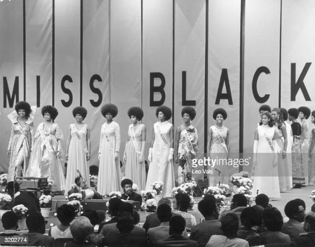 Contestants for the Miss Black America pageant line up on stage in front of a panel of judges during the evening gown competition