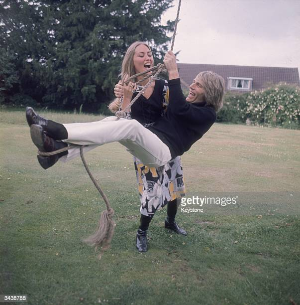 Pop singer and actor Adam Faith with his wife Jackie Irving playing on a rope swing in their garden