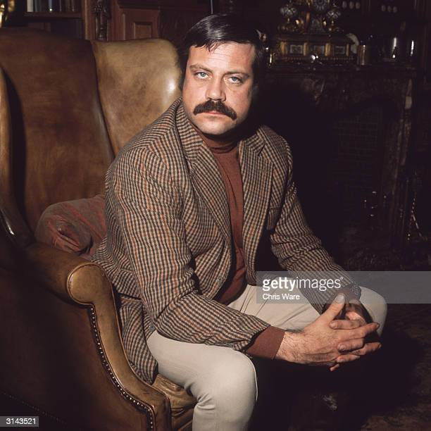 British actor Oliver Reed sitting in an armchair in his huge exmonastery home Broome Hall near Dorking in Surrey
