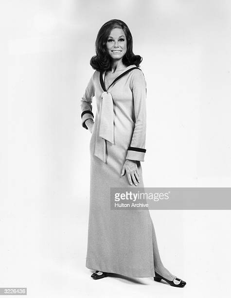 Full-length studio portrait of American actor Mary Tyler Moore. She is wearing a long sleeved, full-length dress which has a nautical collar.