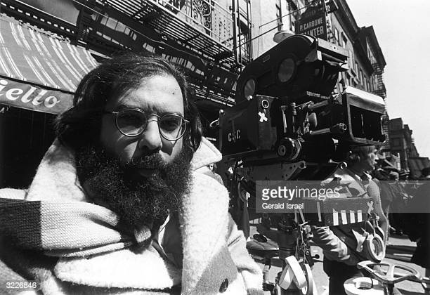 Headshot of American film director Francis Ford Coppola sitting outdoors on a film shoot beside a motion picture camera on a city street Other crew...