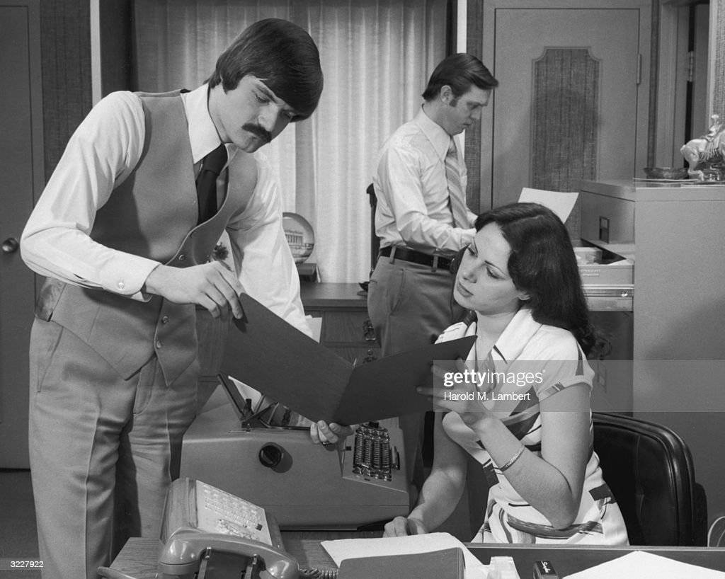 A businessman holds an open file as he speaks to a woman sitting behind a typewriter at an office desk. A man holds a document in the background.