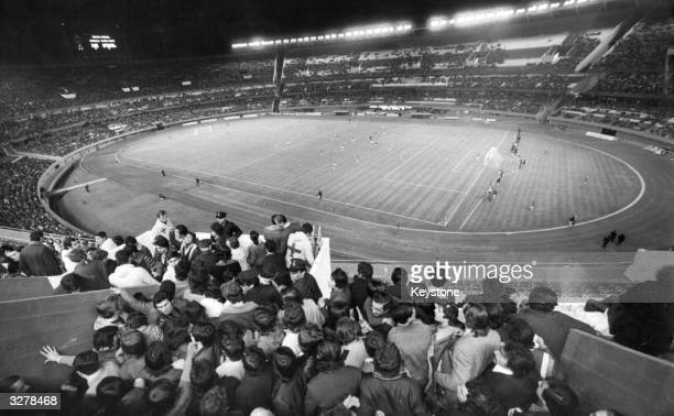 A football game taking place under floodlights inside the River Plate Stadium in Buenos Aires