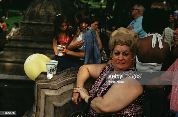 A large and querulous looking New Yorker wearing a large wig is sitting in the park on a summer's day