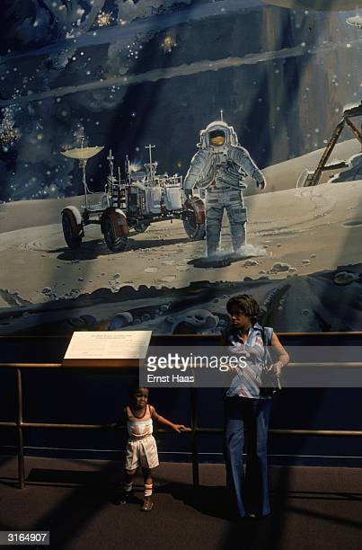 A mother and son lean against a railing ignoring the picture of the moon landing behind them