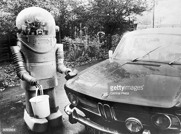 A robot holding a bucket and sponge washes a car