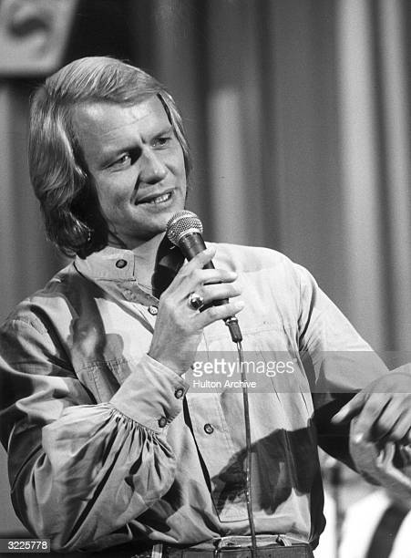 American actor and pop singer David Soul singing into a microphone He wears a shirt with puffy sleeves