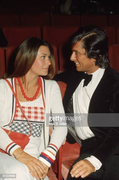 American actor Kate Jackson and film producer Robert Evans smile at each other while sitting in red theater seats Jackson wears a white knit outfit...