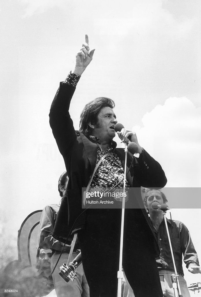 American country singer Johnny Cash (1932 - 2003) sings at a microphone with one hand raised, as two backup singers stand behind him, at an outdoor Campus Crusade for Christ Festival. He wears a black jacket, and his guitar hangs on a strap behind his back.