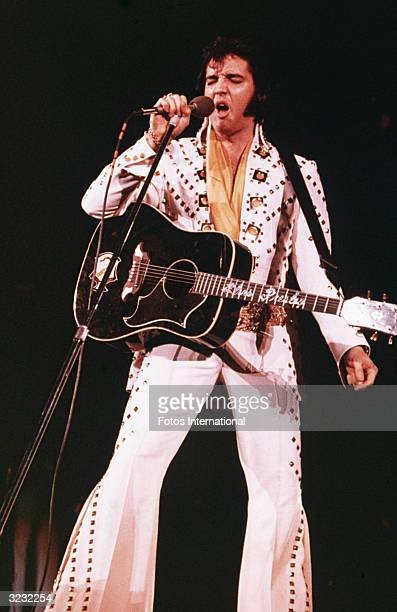 American rock singer Elvis Presley wearing a white rhinestonestudded suit and strapped guitar singing into a microphone with his eyes closed