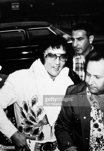 Circa 1975 American singer and actor Elvis Presley surrounded by bodyguards smiles after getting out of a limousine 1970s