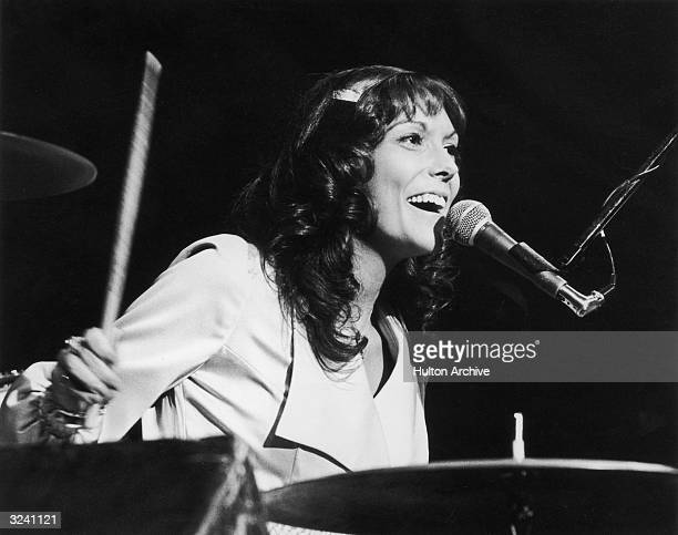 American singer and musician Karen Carpenter of the soft rock duo The Carpenters plays the drums while singing into a microphone