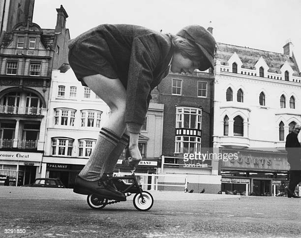 Barry Lapworth of Hastings cycles on a miniature bicycle along the seafront.