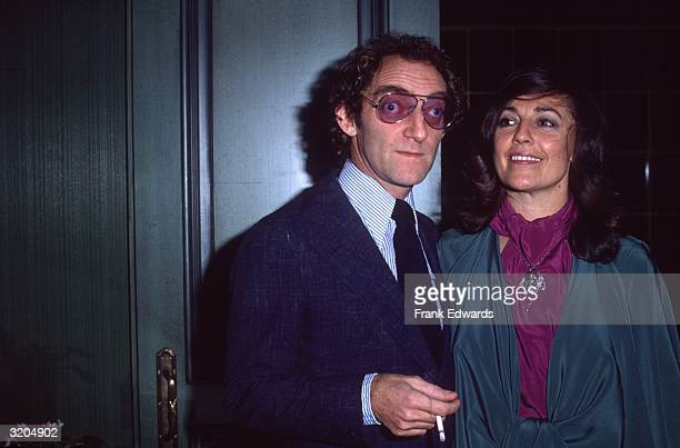 British actor Marty Feldman smokes a cigarette while standing with his wife Lauretta Sullivan Feldman is wearing sunglasses with purple tinted lenses...