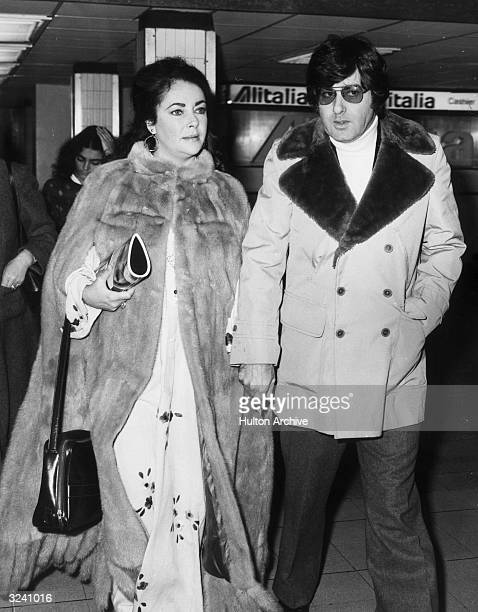 Britishborn actor Elizabeth Taylor and American used car salesman Henry Wynberg walk through an airport holding hands She wears a long fur coat