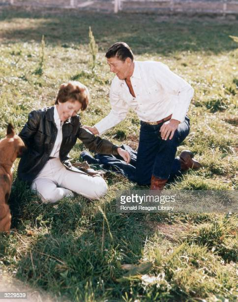 California governor Ronald Reagan kneels in the grass and holds his wife Nancy's arm laughing as they play with a dog on the Yearling Row Ranch...