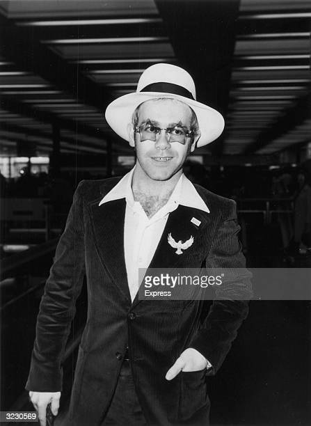Candid portrait of British pop musician Elton John wearing star-shaped sunglasses and a hat at an airport.