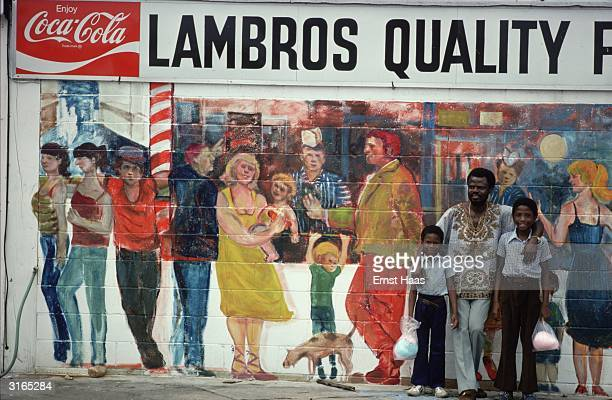 Carrying their shopping a man and his family pose in front of a mural which advertises a food store and shows a group of shoppers