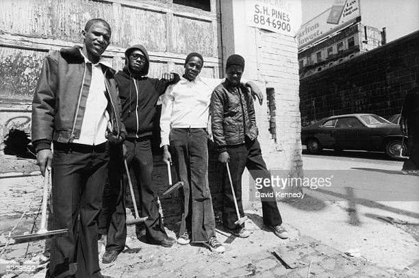 Four young AfricanAmerican boys pose together outside of a garage holding their brushes for washing car windows New York City They wear bell bottoms...