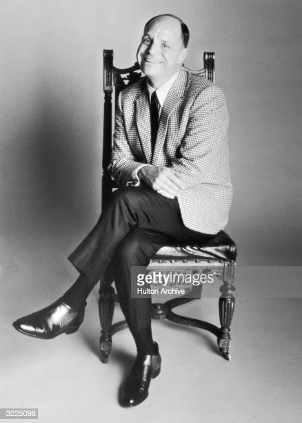 Fulllength portrait of American comedian and actor Don Rickles sitting in a chair with his legs crossed