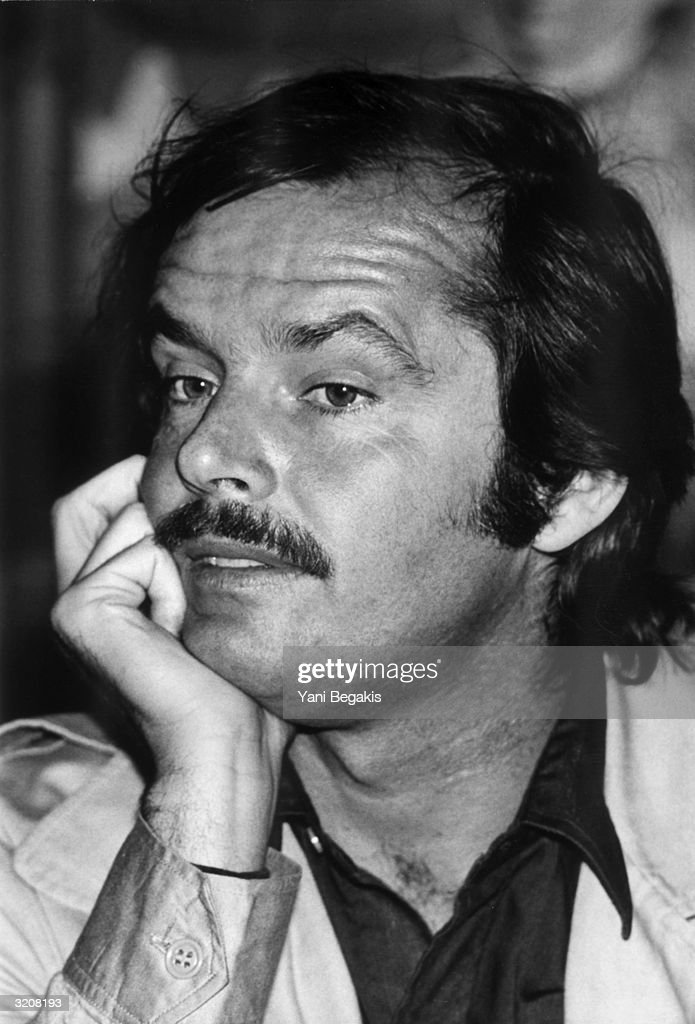 Headshot of American actor Jack Nicholson with a moustache, resting his head on his hand.