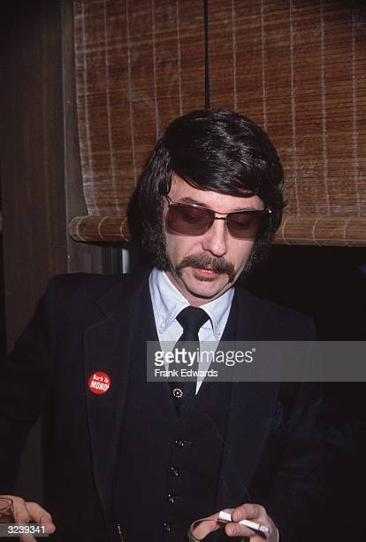 Headshot of American music producer Phil Spector in dark glasses and wearing a badge that reads, 'Back to MONO.'