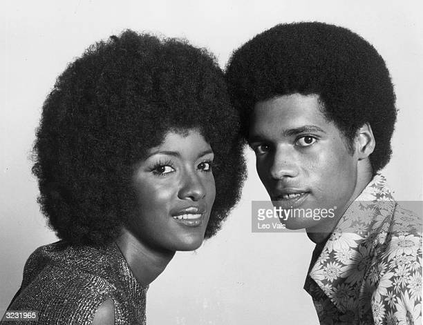 Headshot studio portrait of an AfricanAmerican couple both with Afros The woman wears a metallic tank shirt and the man wears a flowerprinted...