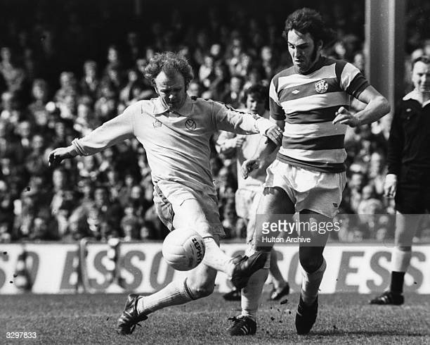 Leeds United football player, and captain of the Scottish national side, Billy Bremner tackling Queens Park Rangers player, and England skipper,...