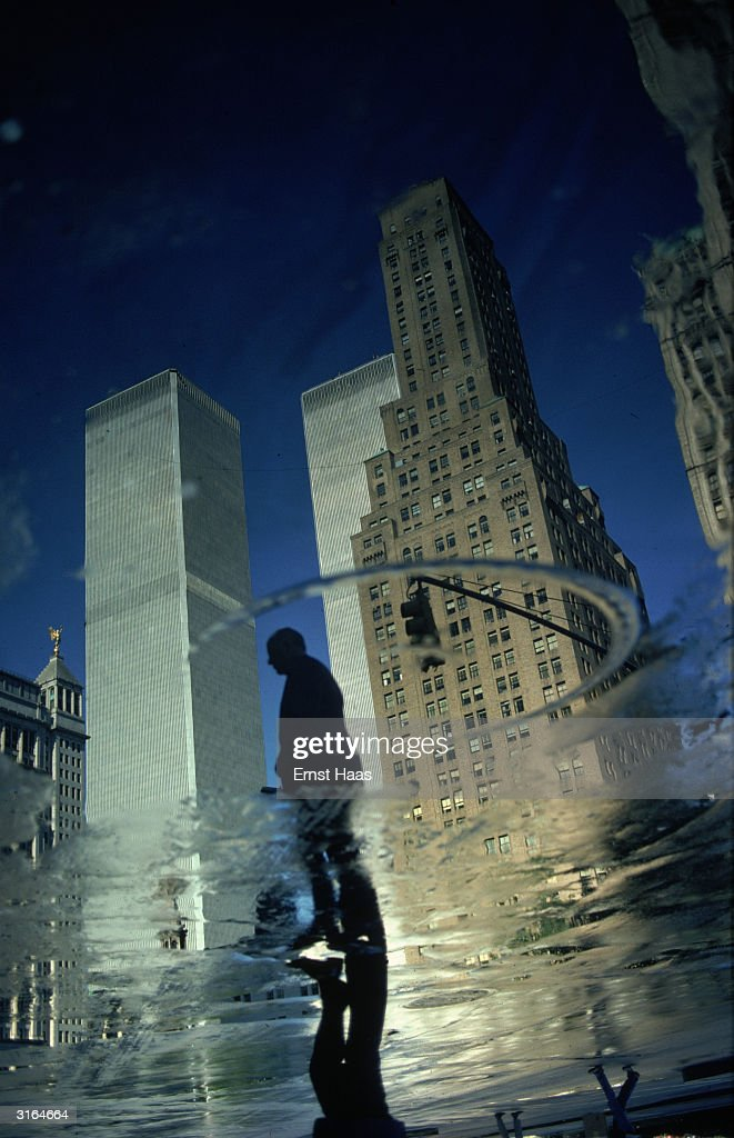 New York skyscrapers, including the World Trade Center (World Trade Centre), reflected in a puddle of water on the street. Haas intended the image to be this way up.