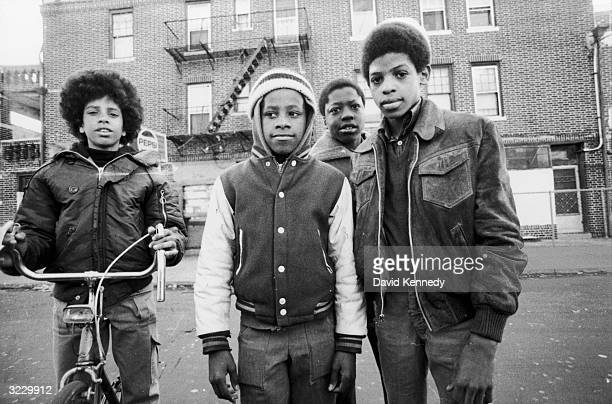 Portrait of four AfricanAmerican boys standing in the street looking at the camera One of the boys sits on a bicycle Another wears a ski cap over his...