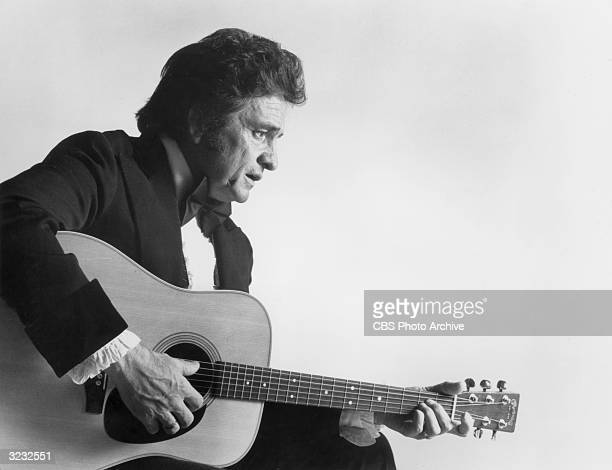 Profile of American country singer Johnny Cash wearing a tuxedo playing an acoustic guitar in a promotional still for the 11th annual Country Music...