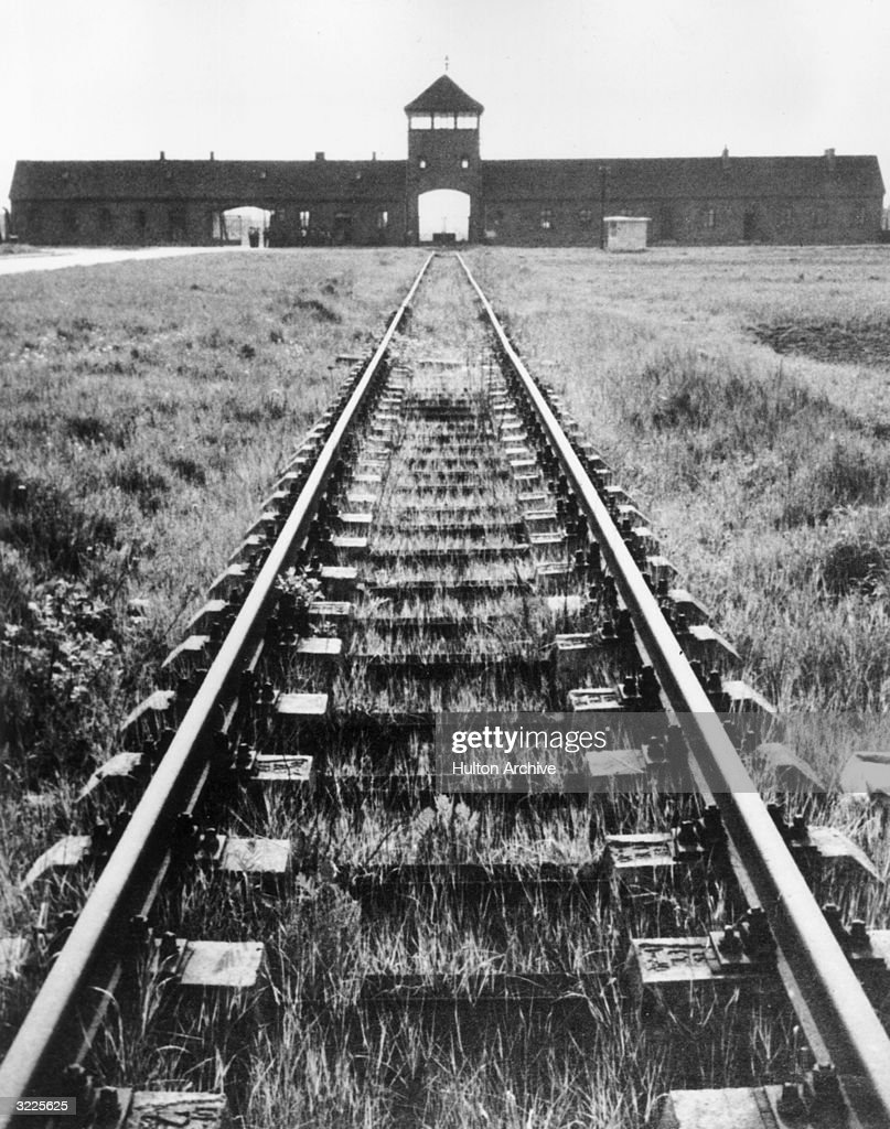 Railway tracks lead into the entrance of the Auschwitz concentration camp, Auschwitz, Poland.