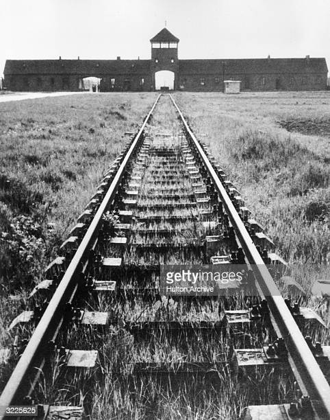 Railway tracks lead into the entrance of the Auschwitz concentration camp Auschwitz Poland
